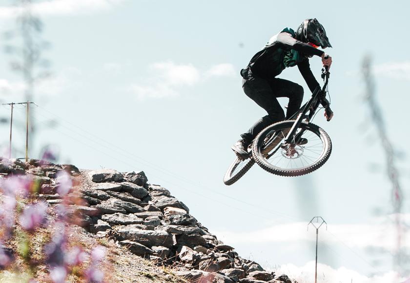 Acrobazie di un rider durante downhill sulle Alpi