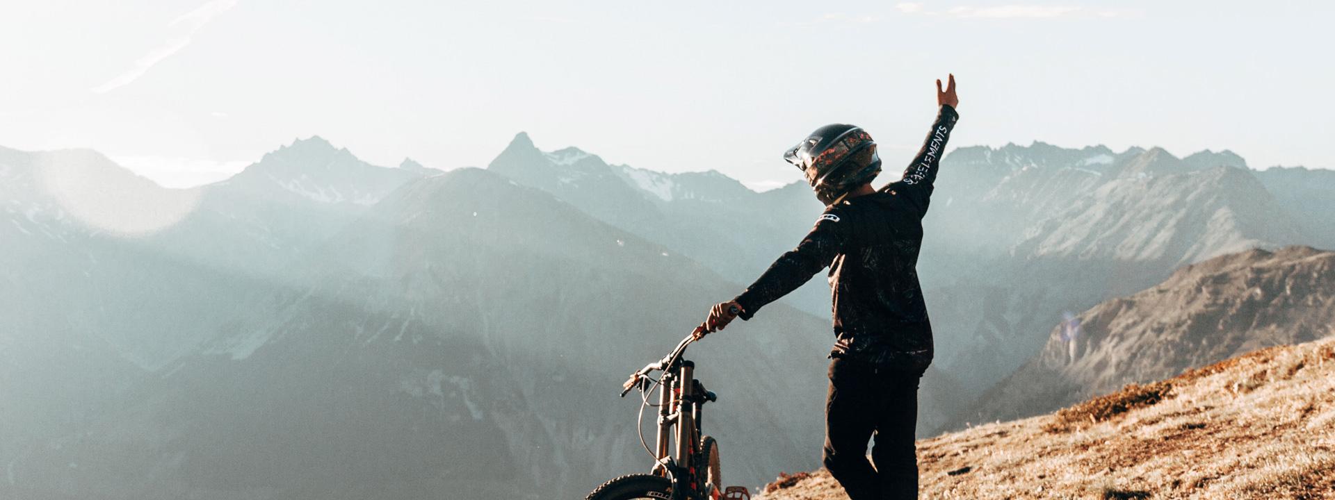 Biker al tramonto che guarda l'orizzonte dal Bikepark Mottolino a Livigno