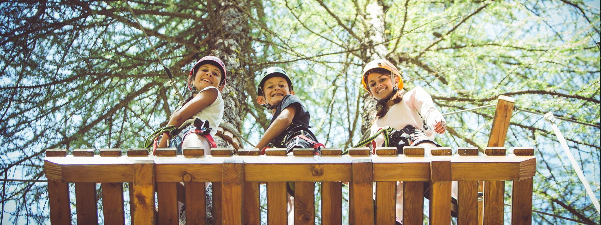 Ragazzi che si divertono sui percorsi in cima agli alberi del Larix Park a Livigno