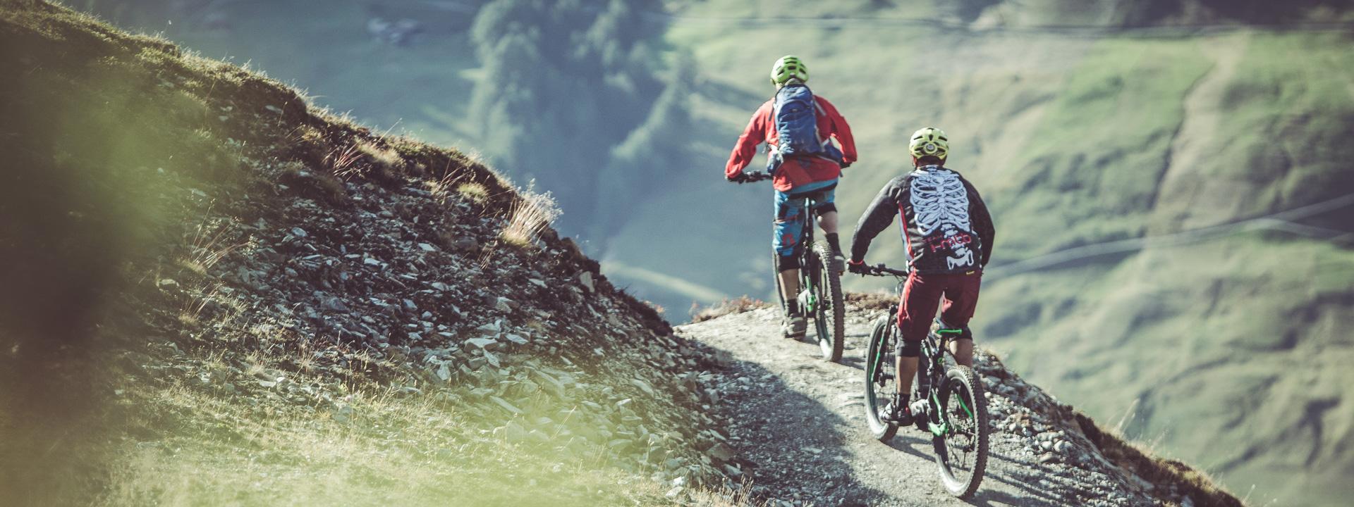 Bikers su sentiero che conduce verso l'Alpe Mine a Livigno dal Mottolino Bikepark con MTB