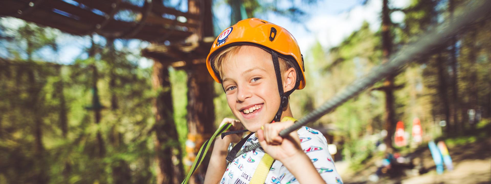 Bambino sorridente sul percorso verde del Larix Park del Mottolino a Livigno