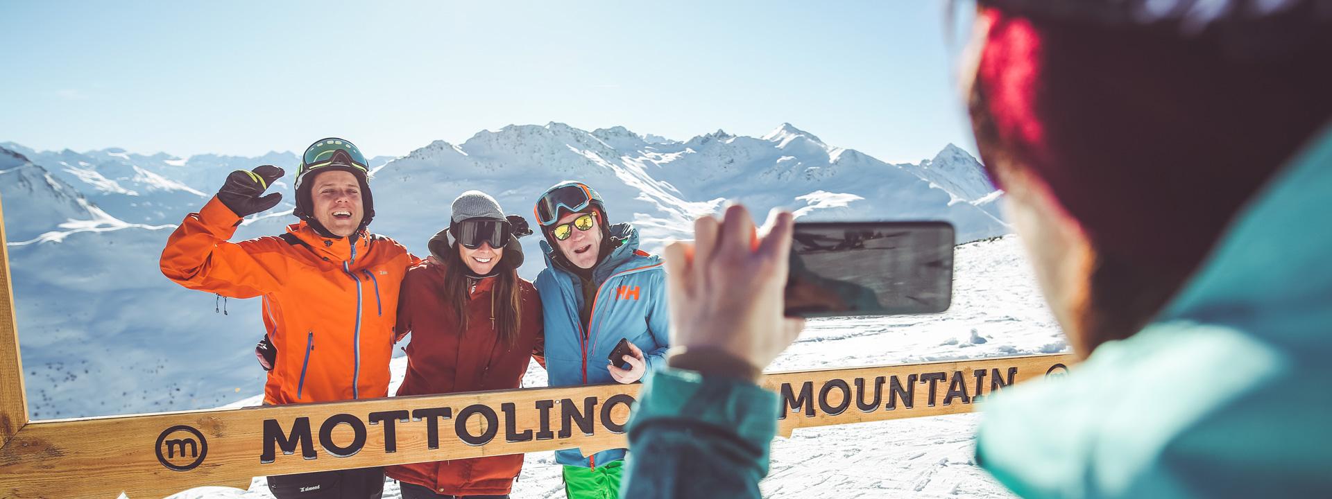 Gruppo di amici che si fanno una foto in cima alla ski area Mottolino a Livigno