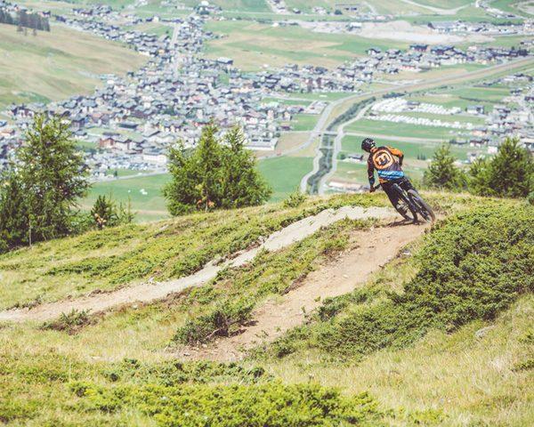 Biker su sentiero del versante Mottolino con bici da Enduro verso la valle di Livigno